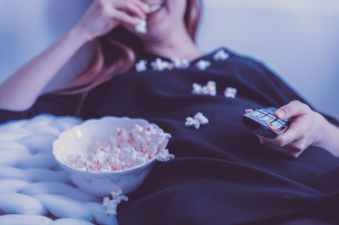woman wearing black dress shirt eating popcorn